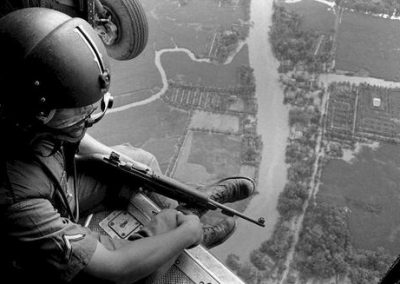 U.S. Helicopter Crewchief Watches Ground Movements of Vietnamese Troops