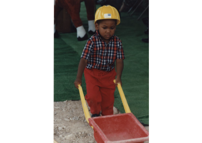 Little boy, dressed as a construction worker with plastic wheelbarrow, at the ground breaking for the Eccles Lab School building.