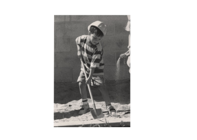 Boy practices digging with a shovel in preparation for the Eccles Lab School Building Dedication Ceremony.