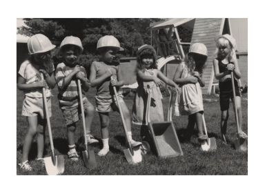 Children standing in front of the UTC Day Care practicing digging with shovels and a small wheelbarrow. This is in preparation for the Eccles Lab School Building Dedication Ceremony.