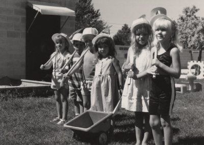 Children standing in front of the UTC Day Care practicing digging with shovels and a small wheelbarrow.