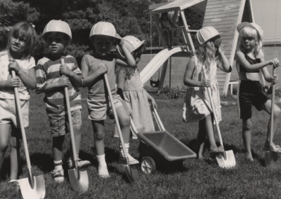 Children standing in front of the UTC Day Care with shovels and a small wheelbarrow.
