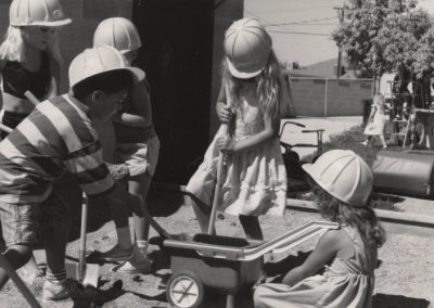 Children practicing digging with shovels and a small wheelbarrow at the UTC Day Care.