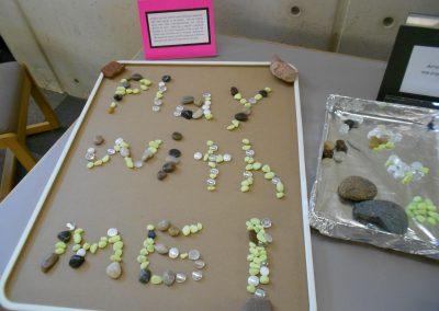 "Rock arranging station. Someone used the rocks to spell out ""play with me!"""