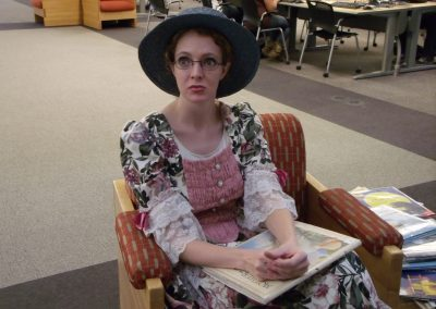 """Andrea Egbert posing as """"Mother Goose"""" reading to gathered children"""