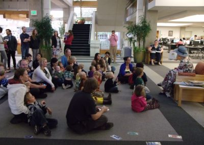 "Andrea Egbert reading ""Mother Goose"" to gathered children in the Markosian Library"