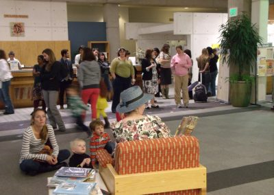 """Andrea Egbert reading """"Mother Goose"""" to gathered children in the Markosian Library"""