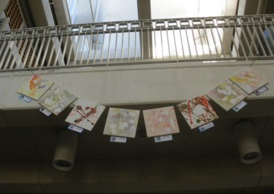 A string of splatter paintings, made by the children at the Eccles Lab School, hang from the second floor balcony.