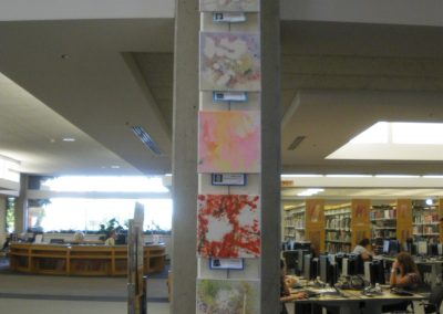 Paintings, made by the children at the Eccles Lab School, are hung on a supporting beam in the Markosian Library.