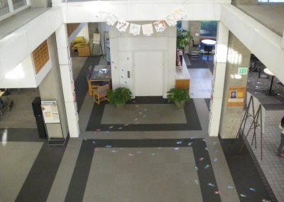 Aerial view, from the second floor balcony, of the colored foot and hand prints on the floor and wall.
