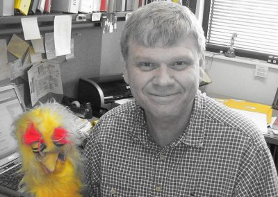 Dale Smith, Associate Dean, and very involved with the Eccles Lab School, poses at his desk with a chicken hand puppet.
