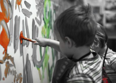 Kids paint on a large surface at the Eccles Lab School.