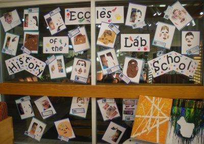 History of the Eccles Lab School exhibit sign. Which the kids at the school have garnished by making art around the sign itself.