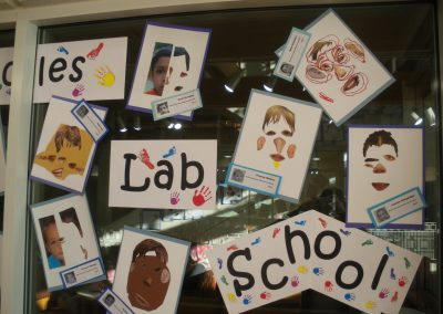 Close up of the Lab School sign along with some of the paintings made by children who attend the Eccles Lab School.