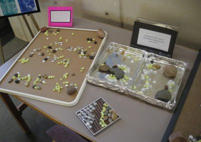 On a table are several rock arranging stations.