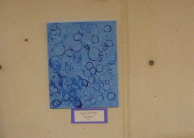 "The Panda Bear class at the Eccles Lab School made a group painting which is called ""Blue Bubbles"" which is dark blue circles on a lighter blue field."