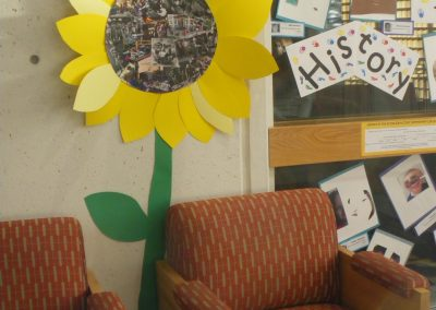 A paper sunflower on the wall with photographs of moments from the Eccles Lab Schools past and latest developments.