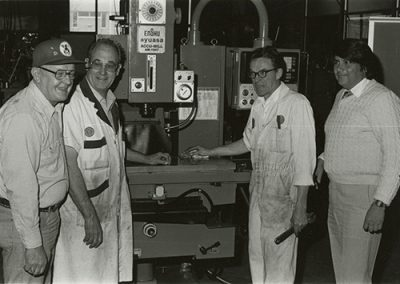 Teachers, instructors and/or associate instructors stand in front of a Enshu Accu-Mill Model AM-1547 metal working machine. Photo likely taken between 1960-1970.