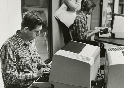 Individuals in computer lab learn about programming and data entry. Photo likely taken between 1975 and 1985.