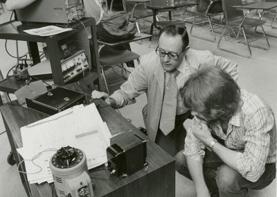 Teacher and students examine glass tube television to see if it can be repaired. Digitization completed with funds from a 2017 USHRAB (Utah State Historical Records Advisory Board) Grant that was awarded to Salt Lake Community College, Library Services. Photo likely taken between 1960-1977.