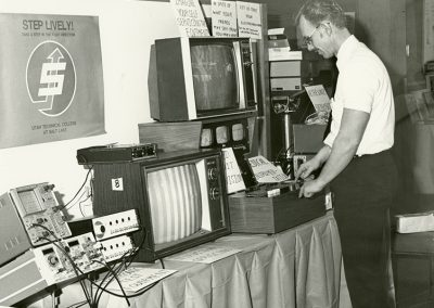 A Display that invites students to learn about servicing electronic devices. It also invites individuals to bring broken electronic devices (televisions, etc.,.) to be fixed by students enrolled in the program. Photo likely taken between 1960-1977.