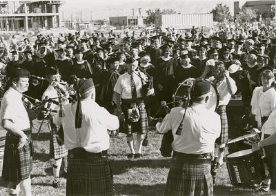 Photo, in black and white, shows bag pipe players standing in a circle with teachers in commencement regalia. All in support of Student Body President Dave Carlson who had been seriously injured in a car accident.