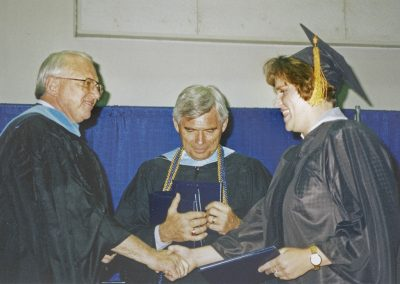 Commencement ceremony where student receives her diploma as Judd Morgan (Interim President between 2003 and 2005) stands in the middle.