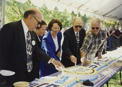 Frank W. Budd (President 1991-2000) and other individuals of particular note for SLCC all cut the celebration cake together. Photo taken September 9, 1998.