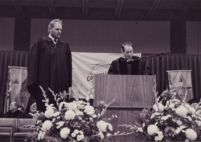 Past Utah Jazz basketball player, Mark Eaton (7 ft 4 in), receiving an honorary degree from Salt Lake Community College.