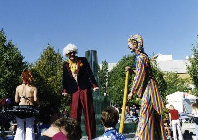 Circus-like performers on stilts, that also play didgeridoos, wander around at the Salt Lake Community College Convocation Festivities Of 2000.