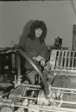 Lucy uses a Baumfolder which is a machine for bindery, finishing, packaging paper products. Photo likely taken between 1975 and 1990.