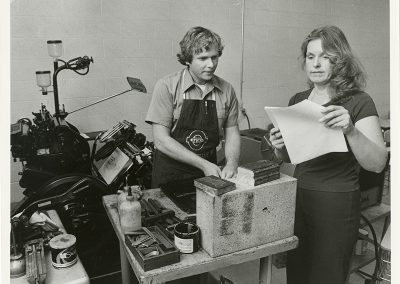 Student at letterpress station with teacher. Photo likely take between 1980 and 1990.