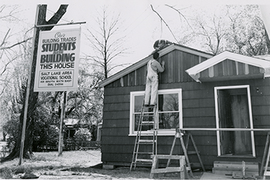 "Students outside working on the roof and siding of the nearly completed house with the sign next to it. which says: ""Our building trades students are building this house; Salt Lake area vocational school, 431 South 6th East, Dial 3-4594."" Photo taken between 1954 and 1955."