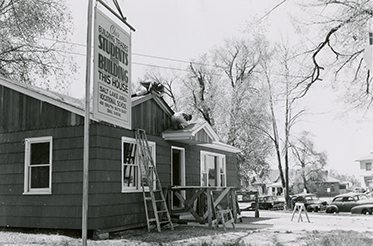 Student built house is almost complete. Photo from 1954 or 1955 (notice cars from the period in the background).