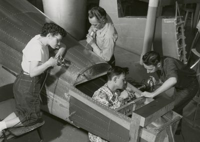 "Eva Van Gerven, Richard Tilt, Teddy Hiatt, and Lynn Liston riveting and drilling in ""skinning"" on an airplane fuselage. Digitization completed with funds from a 2017 USHRAB (Utah State Historical Records Advisory Board) Grant that was awarded to Salt Lake Community College, Library Services. Photo likely taken between 1947-1957."