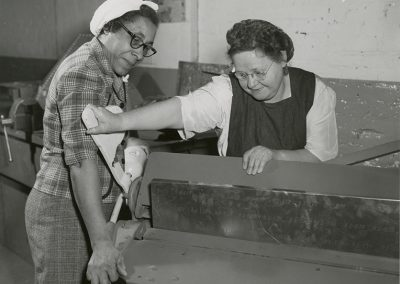 "Mrs. Almira Wheeler and Mrs. ""Pete"" Petersen demonstrating how to use a metal sheet bending machine. Photo likely taken between 1955-1970."