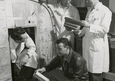 Instructor William Waggoner (standing left) explaining a feature of sheet metal work to Parker Pratt, Martin Rubisch and DeRay Parker (standing right). All four are rated pilots. Photo likely taken between 1950 and 1960.
