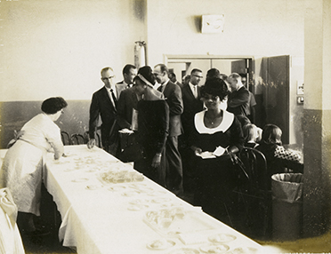 Students, teachers and administrators file into a room set up with refreshments. At the Salt Lake Community College Commencement, August of 1965. This is when the school was known as Salt Lake Trade Technical Institute.
