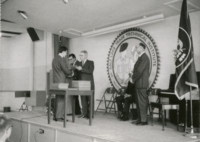 Handing off of the diplomas with Jay L. Nelson (who was school President between 1949 and 1978) waiting to give a congratulatory handshake. Photo taken in August of 1965.