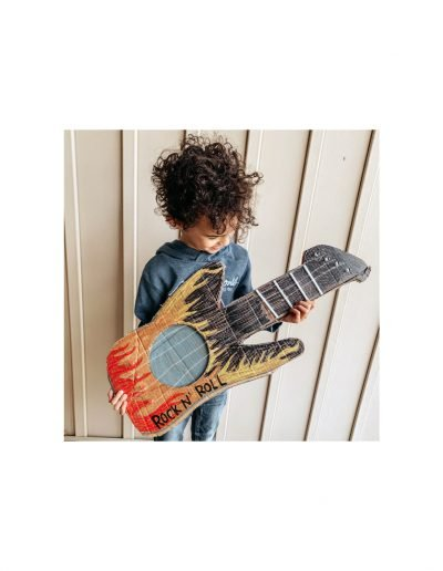 boy holding cardboard guitar