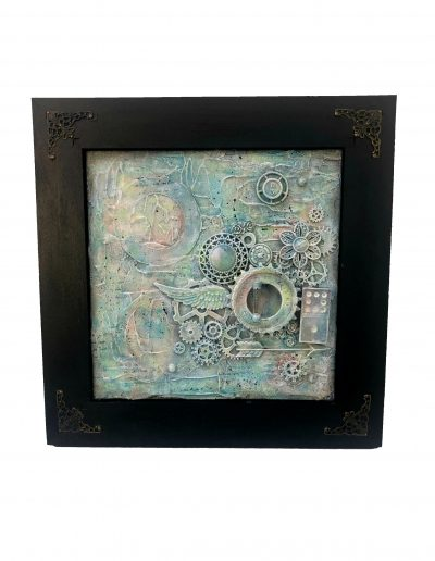 collage of upcycled materials in black frame