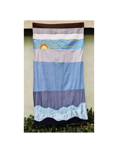tapestry of sun rising above horizontal stripes of different grey and blue fabrics