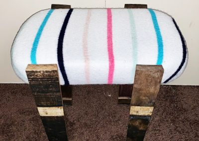 upcycled stool made from a thrifted sweater, and upcycled foam, refuse wood, wine barrel and screws.